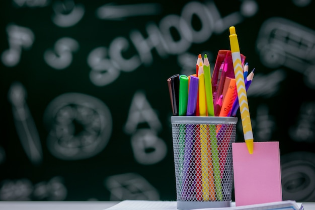 School background with stationery accessories. books, globe, pencils and various office supplies lying on the desk on a green blackboard background
