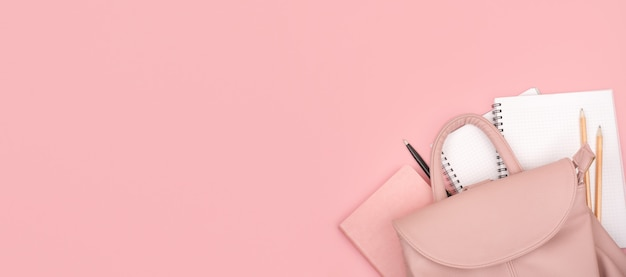 Школьный рюкзак и канцелярские товары на розовом. скопируйте пространство.