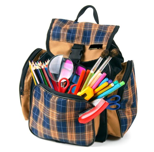学校のバックパックと学校の道具。白い背景に。