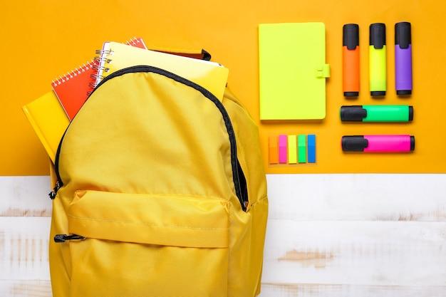Школьный рюкзак и канцелярские товары на цветном фоне