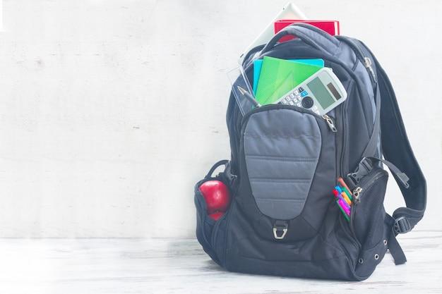 白いデスクトップ上の物資でいっぱいの学校のバックパック