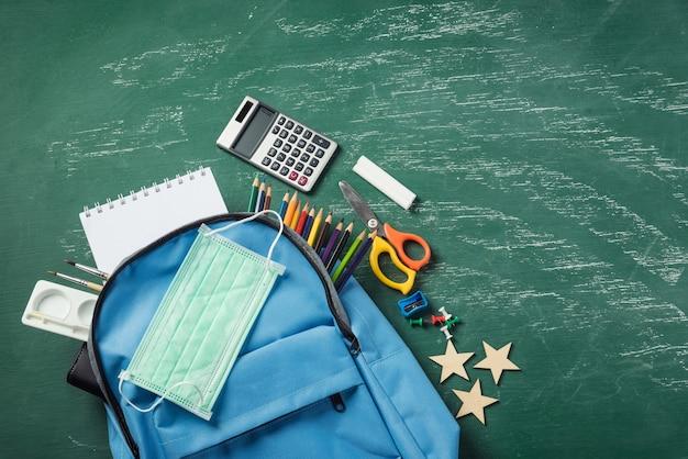 Школьный рюкзак на зеленой доске с защитной маской