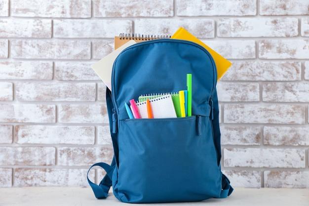 Школьный рюкзак на столе у кирпичной стены