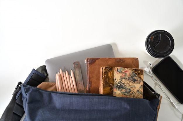 School backpack and school supplies on white wood table background