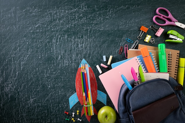 School backpack and supplies with chalkboard background. back to school.