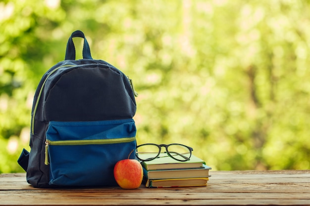 School backpack with books on wooden table and nature background