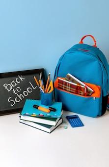 カラフルな学用品と学校に戻る手紙が入った黒板が入った学校のバックパック。青い背景の学用品。バナーデザイン