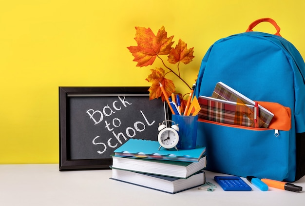 カラフルな学用品と学校に戻る手紙が入った黒板が入った学校のバックパック。黄色の背景に学用品。バナーデザイン