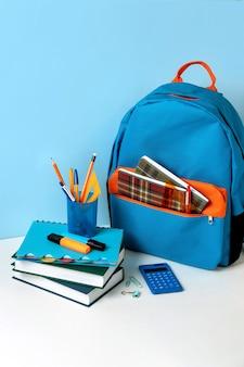 青い背景にカラフルな学用品が付いている学校のバックパック。バナーデザイン