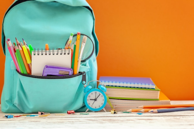 School backpack with different supplies and alarm clock on orange background.