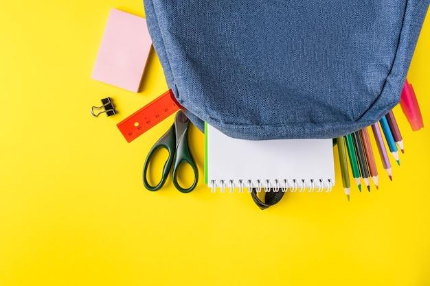 Школьный рюкзак с канцелярскими принадлежностями на желтом фоне. место для текста.