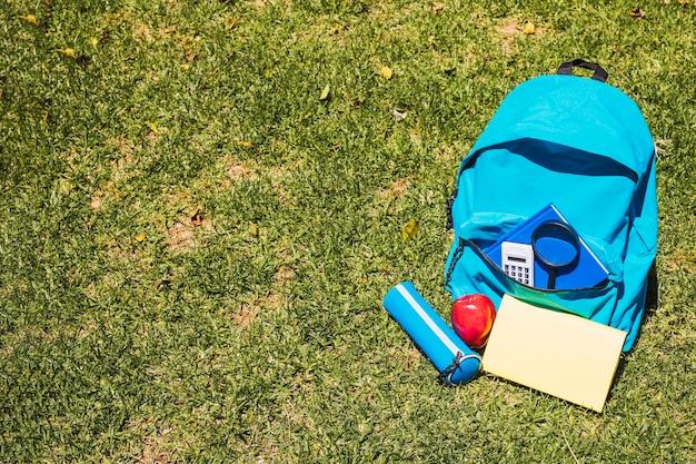 文房具の芝生の上で学校のバックパック