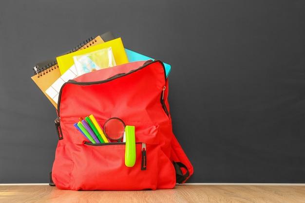 Школьный рюкзак с канцелярскими принадлежностями на столе в классе