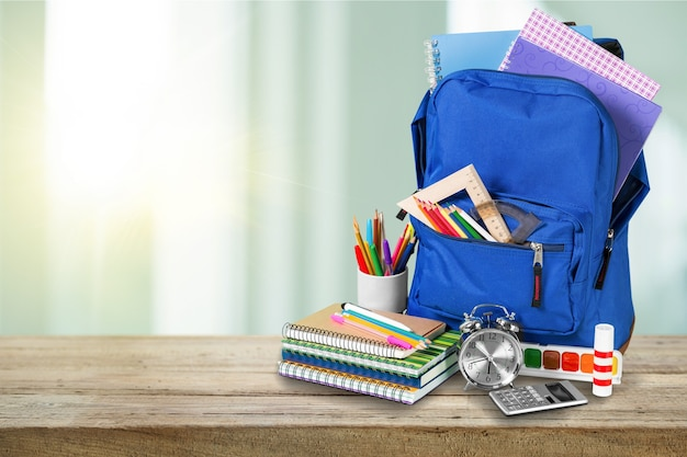 Школьный рюкзак с канцелярскими принадлежностями на деревянном столе
