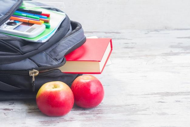 Школьный рюкзак с принадлежностями и яблоками на белом деревянном столе