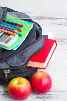 Школьный рюкзак с принадлежностями и двумя яблоками на белом рабочем столе крупным планом