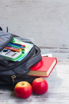 Школьный рюкзак с принадлежностями и двумя яблоками на белом рабочем столе
