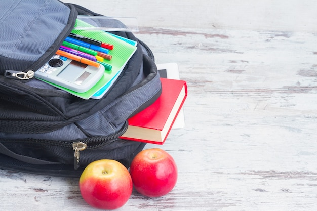 School backpack with supplies and apples on white desktop