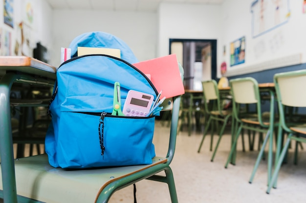 School backpack with supplies on chair