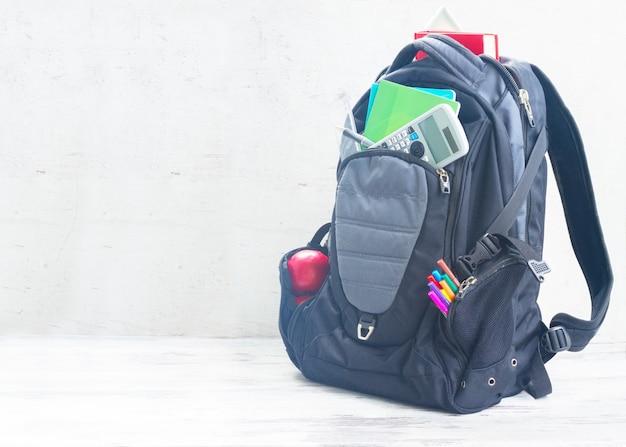 Школьный рюкзак с принадлежностями на белом рабочем столе