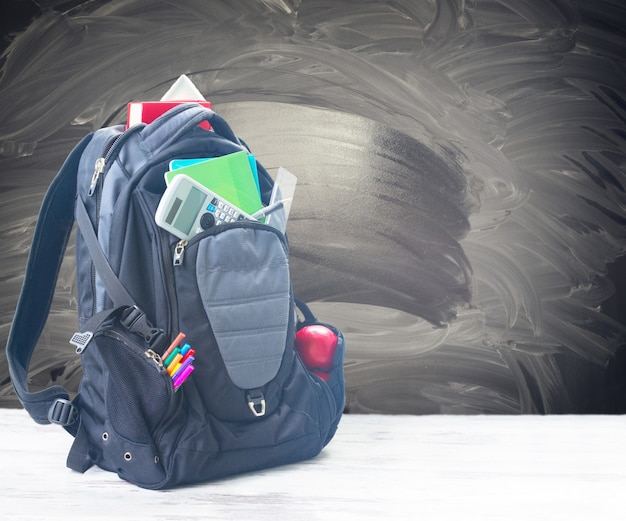 School backpack with supplies on white desktop with empty blackboard