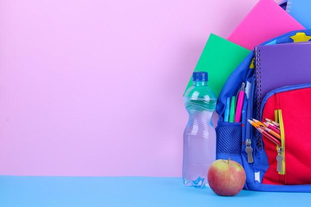 水と明るい背景にリンゴと学校のバックパック