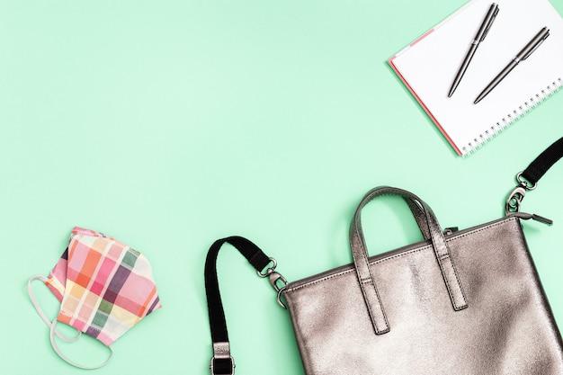 Школьная сумка и школьные принадлежности: блокнот, ручки и медицинская маска для лица.