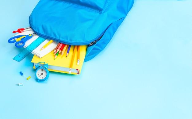 Школьная сумка. рюкзак с принадлежностями для школы на синем фоне. скопируйте место для текста