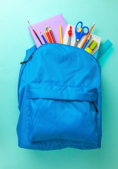 School bag. backpack with supplies for school on blue background. copy space for text.