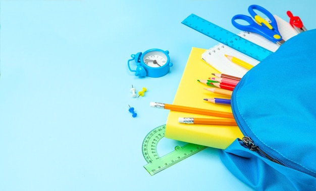 School bag. backpack with supplies for school on blue background. copy space for text
