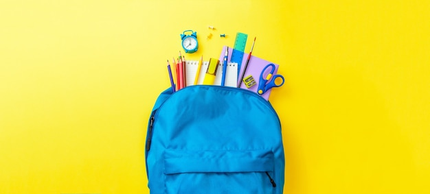 School bag. backpack with supplies for school on yellow background. copy space for text.