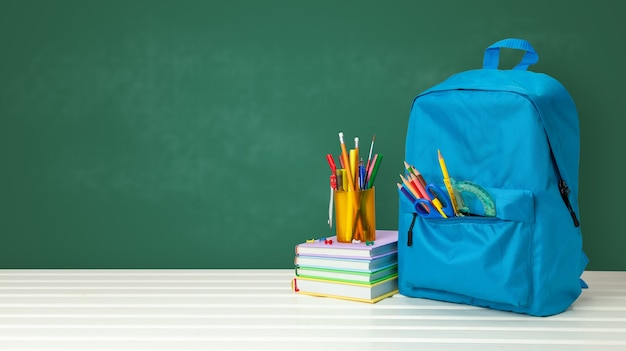 School bag with supplies for school on blackboard background. copy space for text.