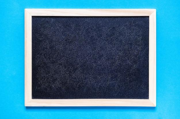 水色の背景に学校の黒い黒板テキストフラットレイコピースペーストップの空の黒板