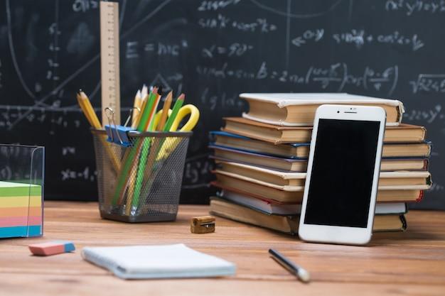 Школьные учебники и канцелярские товары на фоне дерева и классной доски, написанные математическими формулами и уравнениями