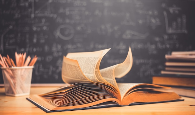 School books on desk formulas and physics inscription on the blackboard