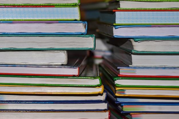 Школьные учебники лежат в две стопки на столе
