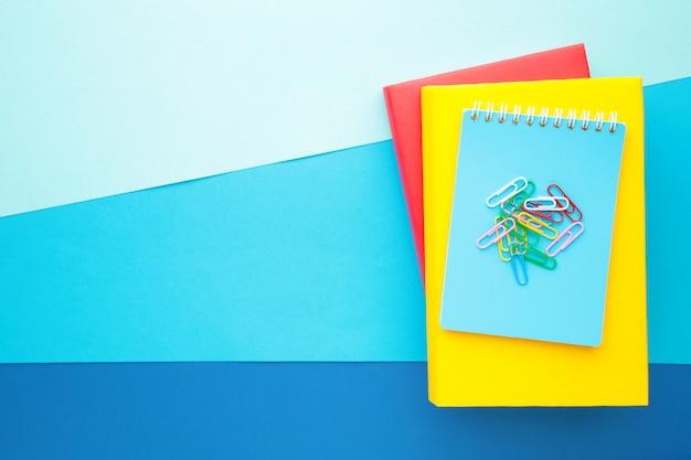 Школьные учебники на синей стене с копией пространства