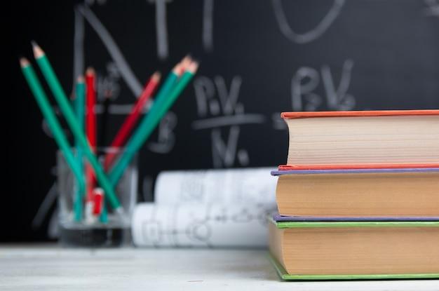 Школьные учебники, карандаши и рисунки на белом столе на доске