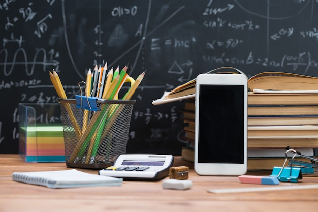 School books and stationery on a wood and a chalkboard background written with mathematical formulas and equations