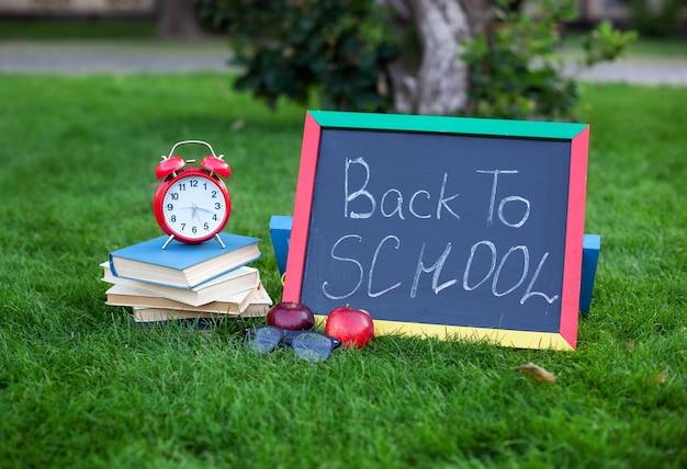 Школьные учебники с красным будильником и доской