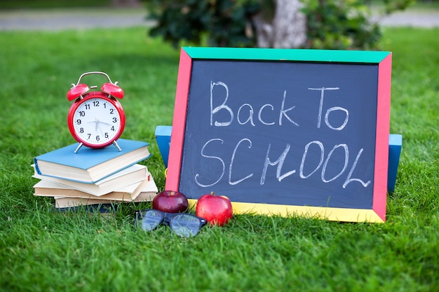 School books with red alarm clock and blackboard with back to school quote