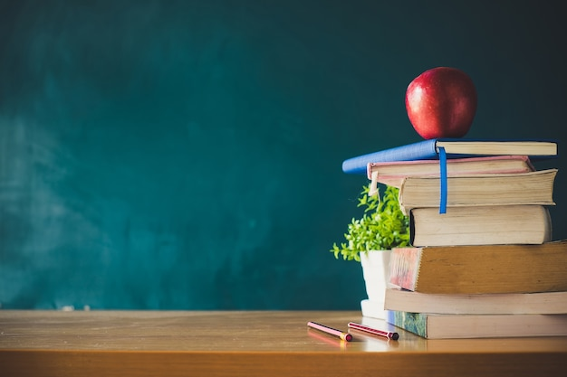 School books with red apple on desk over green school board background