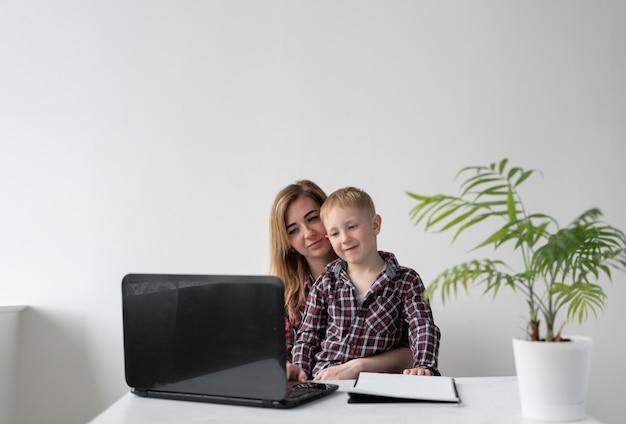 학교 소년과 그의 어머니는 함께 숙제를하고 있습니다. 그들은 테이블에 앉아 노트북에서 작업을 읽고 있습니다. 원격 교육. 부모는 자녀를 학생에게 돕습니다. 온라인 레슨.