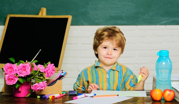 School boy in classroom. little child writing with colorful pencils. elementary school, learning and education.