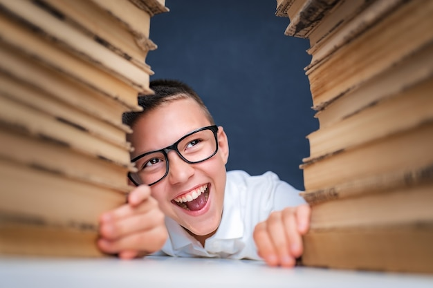 School boy in glasses sitting between two piles of books and look away from camera smiling.