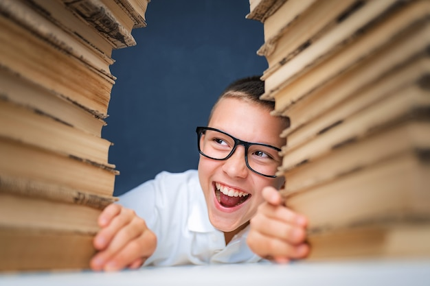 School boy in glasses sitting between two piles of books, smiling