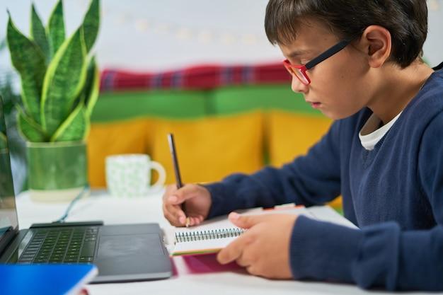 Школьник, имеющий онлайн-классы дома, пишет в блокноте и использует ноутбук