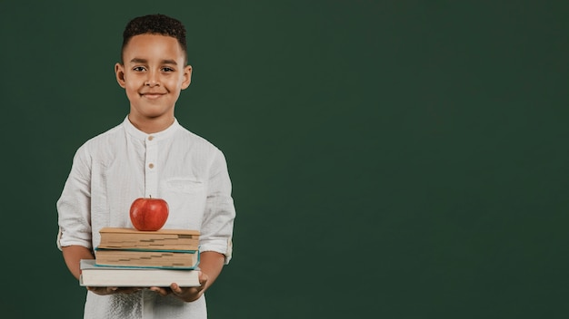 School boy holding books and apple