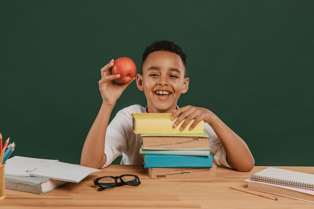 School boy holding a delicious apple