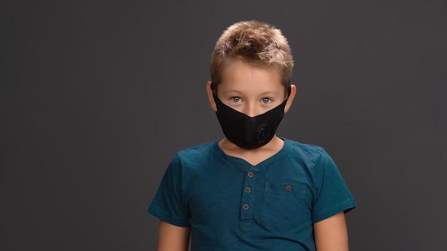 Школьник в черной многоразовой маске для лица и темно-синей футболке с воротником на пуговицах удивлен